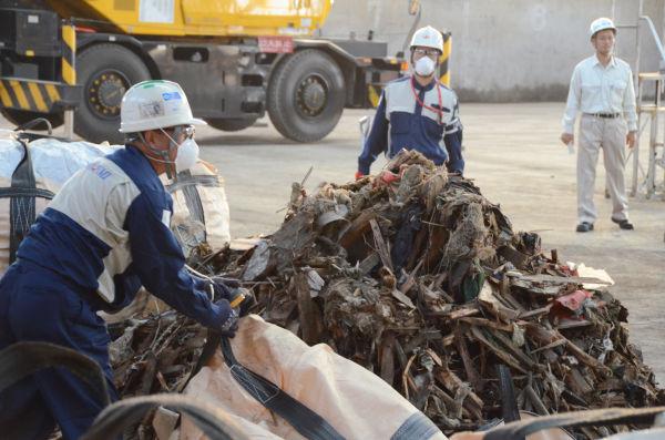 宮城県石巻市から北九州市に到着した瓦礫。作業員がカッターでビニール袋を切り裂くと、土とカビが入り混じったような匂いが鼻をついた。=22日、北九州市日明積出基地。写真:筆者撮影=