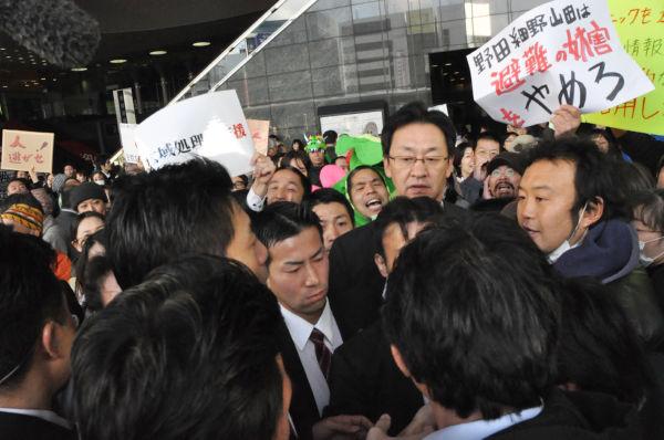 京都駅頭で瓦礫受け入れ反対派に取り囲まれる細野大臣。『避難の妨害やめろ』のプラカードが瓦礫問題の断面を物語る。=3月末、JR京都駅。写真:田中撮影=