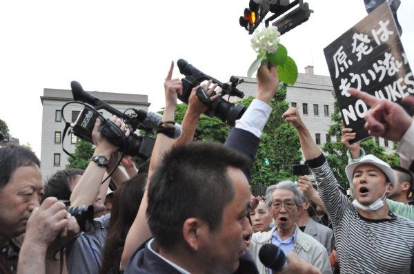 『紫陽花革命』。勤め帰りの男性は、アジサイの花を空に突き上げ「再稼働反対」を叫んだ。=22日夕、首相官邸前。写真:田中撮影=