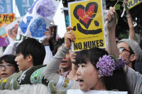 紫陽花革命にちなんでアジサイの花を髪に刺し「再稼働反対」の声をあげる女性。=29日夕、首相官邸前。写真:田中撮影=