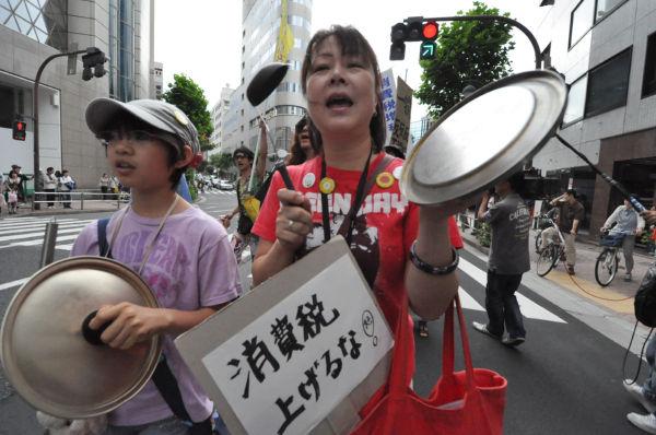 鍋のフタを打ち鳴らし「消費税反対」を呼びかける母と娘。=10日、渋谷。写真:田中撮影=