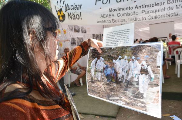 反核テント前で日本の被災地の写真を見る女性。=写真:諏訪撮影=