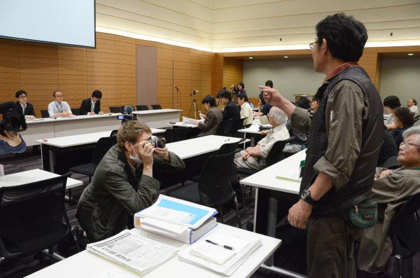 「あなたたちは誰のために仕事をしているのか?」。政府の役人(正面席)を厳しく糾弾する男性は、福島県浪江町から埼玉県への避難者だ。=1日、参院会館。写真:田中撮影=