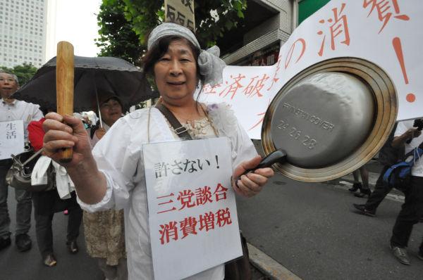 フライパンを打ち鳴らし「消費税反対」を訴える主婦。=17日、池袋。写真:田中撮影=