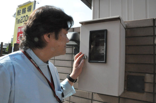 東電の電気メーターをのぞく山崎医師。=写真:筆者撮影=