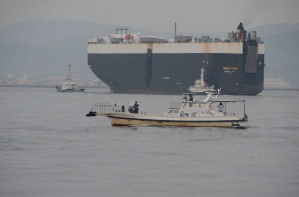 2隻のタグボートに曳航され岩国基地に入港する民間輸送船「グリーンリッジ」(3万2,326トン)。=23日午前5時30分頃、岩国基地沖約2キロ。写真:田中撮影=