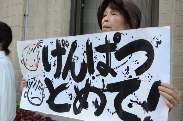左端の似顔絵は孫たち。女性が自分で描いた。悲しそうな目が印象的だった。(24日夕、関電京都支店前。写真:諏訪撮影)