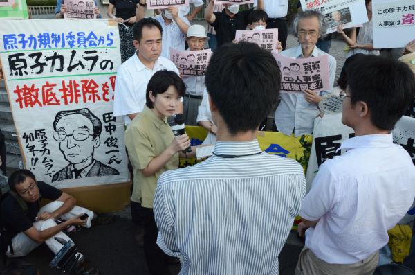 「原子力規制委員会準備室」の役人(後ろ姿)を問い詰める環境団体FoEの満田夏花さん(マイク持つ女性)。=27日夕、内閣府庁舎前。写真:田中撮影=