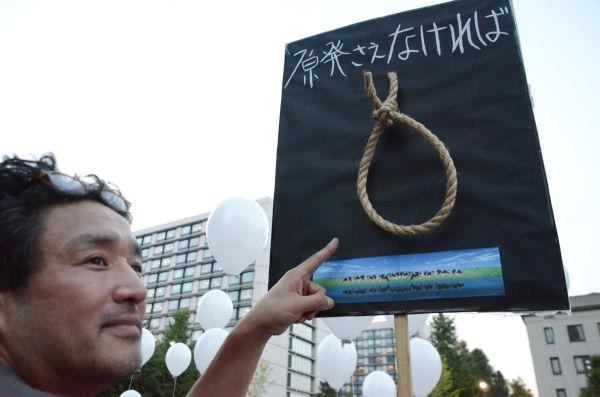 「原発事故で自殺に追い込まれた農民たちの霊を弔いに来た。この悲劇を風化させてはならない」。首吊り縄のオブジジェを製作した男性は表情を引き締めた。=永田町。写真:諏訪撮影=
