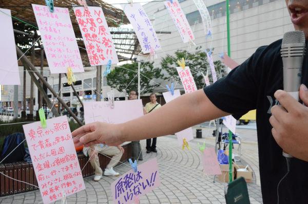 旅行者が書いた短冊が並ぶ青森の金曜集会。=JR青森駅前。写真:諏訪撮影=