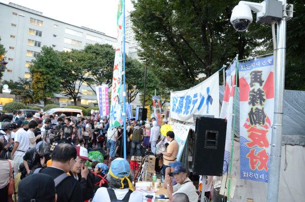 1年を経た経産省前の脱原発テント。当局による監視カメラ(手前)が目を光らせるなか、大勢の市民が集まった。=11日夕、霞が関。写真:田中撮影=
