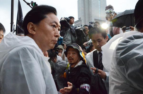 マスコミに揉みくちゃにされながら官邸前に到着した鳩山元首相。元首相が市民と共に現首相に抗議した。鳩山氏は民の声に耳を傾けない野田政権に怒りを露わにした。=永田町。写真:諏訪撮影=