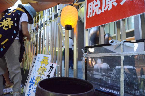 大飯原発の遺影も登場した大阪の金曜集会。=関西電力前。写真:諏訪撮影=