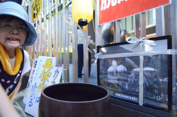 """大飯原発の""""遺影""""が正門の柵に括りつけられた。鉦は関電を成仏させるために僧侶や参加者が打ち鳴らす。=7日夕、関電本店前。写真:諏訪撮影="""