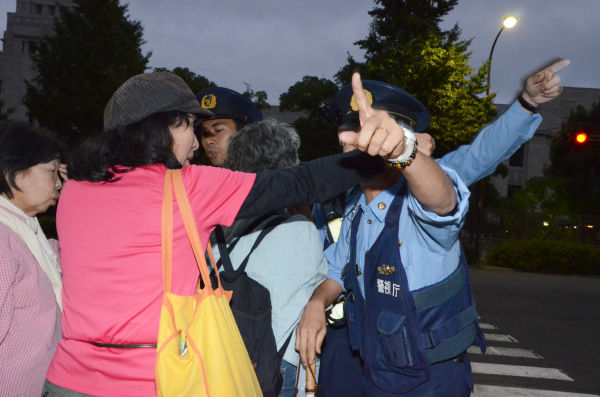 官邸に近づけまいと通せんぼする警察官と揉みあう女性たち。=衆院会館前。写真:田中龍作=