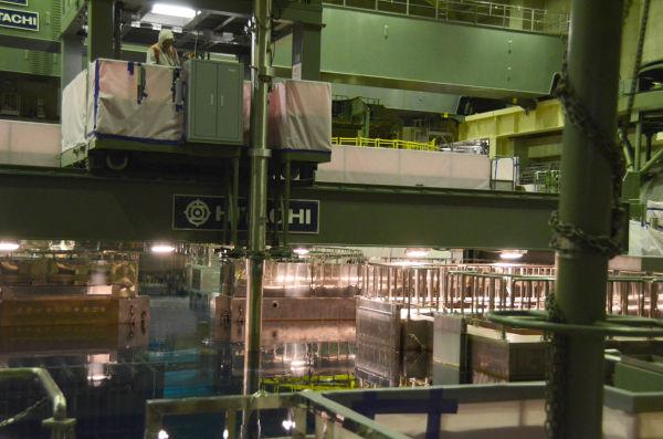 使用済み核燃料はアーム(中央の棒)でつかみ、貯蔵プール(写真手前)に移す。=写真:田中撮影=