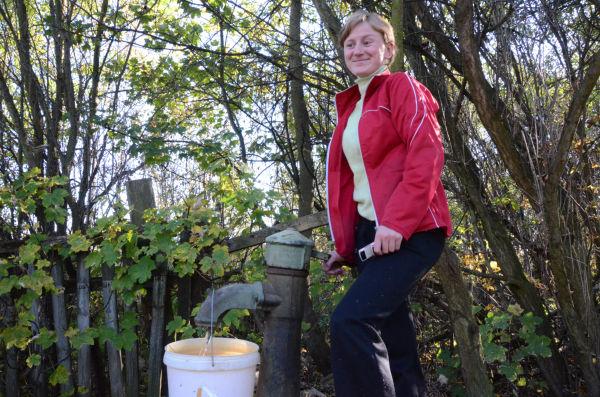 井戸水を汲む主婦は「水の質が悪いので飲み水には使わない」。=写真:田中撮影=