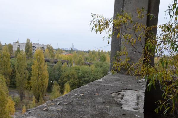 かつての豪華ホテルの最上階から街を望む。原発労働者用のアパートの向こうにチェルノブイリ原発4号機が見える。=16日、プリピャチ。写真:田中撮影