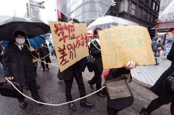 リクルート姿の学生たちは荒縄で体をしばりつけた。「就活したらブラック企業だった」のプラカードも。=23日午後、新宿。写真:田中撮影=