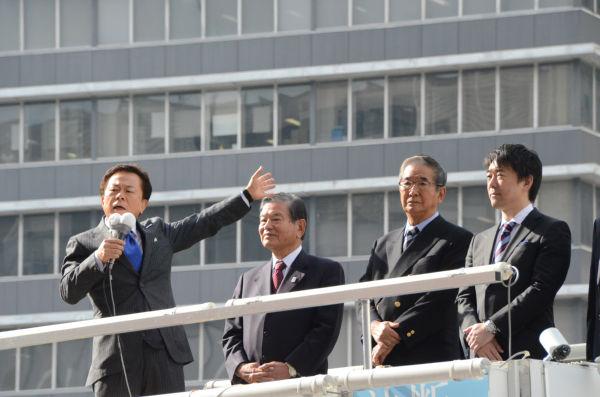 猪瀬直樹候補(左端)は、石原前知事と橋下大阪市長らに見守られながら第一声をあげた。=29日午前11時頃、新宿西口。写真:田中撮影=