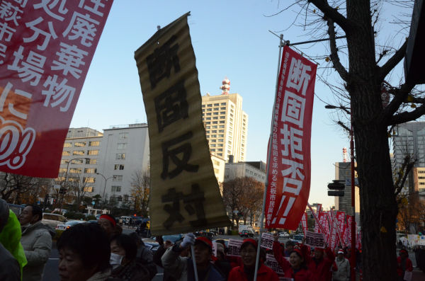 参加者たちはノボリやムシロ旗を掲げ国会に向けてデモ行進した。ムシロ旗の背後にそびえているのが環境省の入るビル。=霞が関。写真:田中撮影=