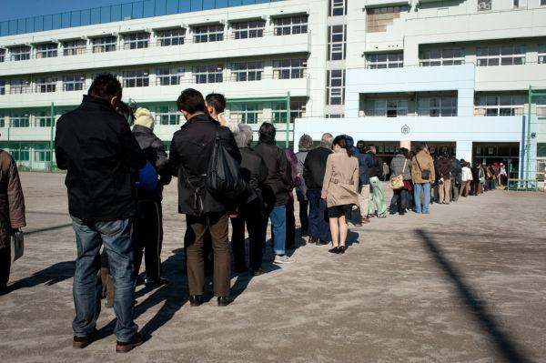 投票所の大半は小中学校の体育館だ。有権者は校庭に並んで =16日正午頃、杉並区杉森中学校。写真:島崎ろでぃ撮影=