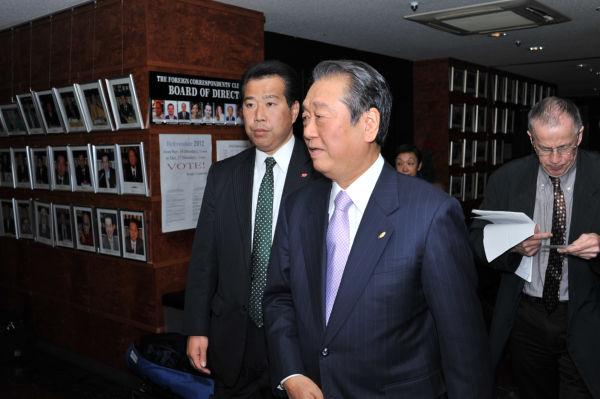 SP(左)に警護されて記者会見に臨む小沢氏。待ち構えていた報道カメラマンが一斉にフラッシュをたいた。=写真:島崎ろでぃ撮影=