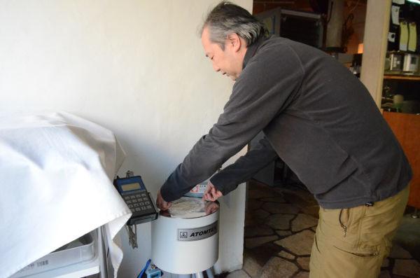 放射能測定する松尾さん。測定は1検体1980円。「なるべく地域に役立てたい」西多摩の土壌汚染マップ作成にも活用している。=オーロラ店内