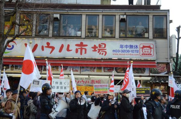 2階のレストランで韓国料理に舌鼓を打っていた観光客も身を乗り出してデモ隊を見つめた。=写真:田中撮影=