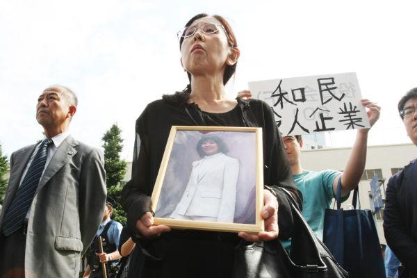 母親の祐子さんは娘の遺影を抱いて抗議に訪れた。後ろのプラカードは「和民 殺人企業」。=写真:山田旬=