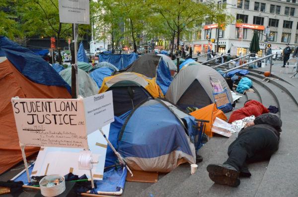 「スチューデント・ローンに正義を」。米国でも奨学金の返済額は莫大だ。借金を払いきれずにホームレスとなる元奨学生も珍しくない。=2011年、ウォールストリート・ズコッティ公園 写真:田中龍作=