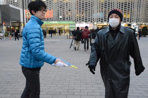 舛添陣営の運動員がビラを渡そうとするが、見向きもしない有権者。=27日、新橋SL広場 写真:筆者=