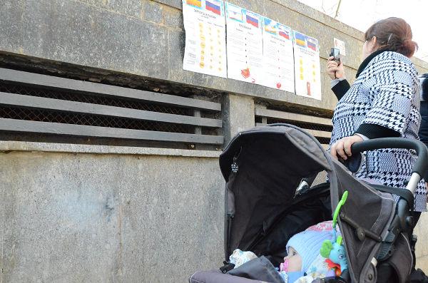 ロシアとウクライナの生活水準を比較した貼り紙広告を携帯電話の内蔵カメラで撮影する母親。=州議会前・シンフェロポル 写真:筆者=
