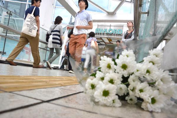 集団的自衛権に反対する女性が現場に花を手向けた。=29日午後、新宿南口 写真:山田旬=