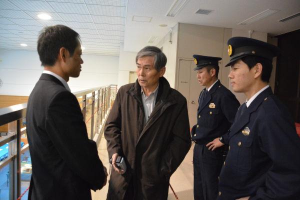 制服警察官を伴った選挙管理委員会の職員(左)は有権者の男性に「ロープの外から出て行くよう」迫った。=14日夜、都内開票所 写真:筆者=