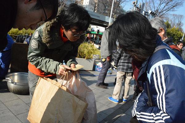 夫と共に訪れた主婦は缶詰やコメなどを差し入れた。左側は支援者。=31日、渋谷区 写真:筆者=