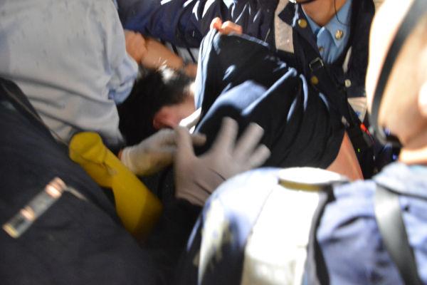 取り押さえられた男性は背中がむき出しになっていた。=16日夜、国会正門前 写真:筆者=