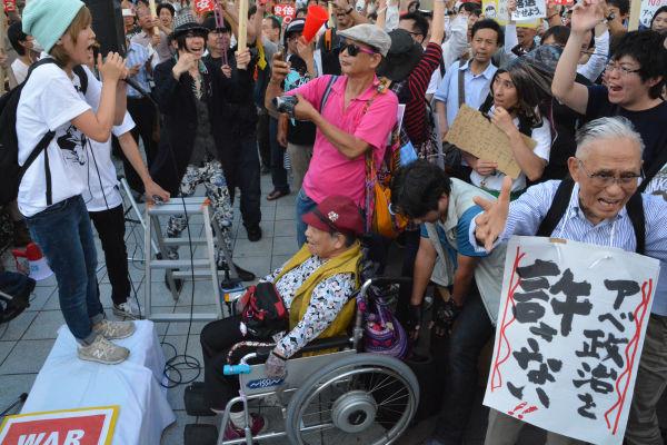 老いも若きも。男性(右端・手前)は学生のコールに合わせて手を振り声をあげた。=27日、名古屋駅西口 写真:筆者=