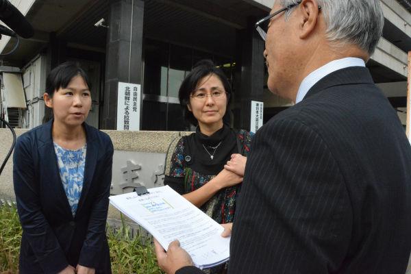 自民党本部ビルの管理者に署名を渡し「国会を開くよう」求める鷹巣さん(右)と川合弁護士。=23日、自民党本部前 写真:筆者=