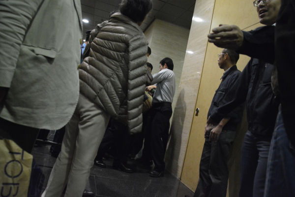 裁判所職員から力づくで法廷の外に出されていく傍聴者。=26日、東京高裁 写真:筆者=