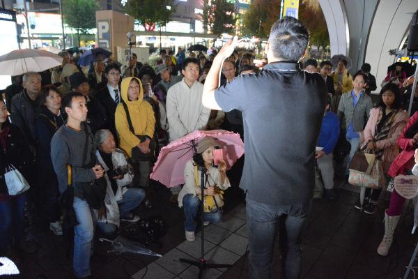 雨のなか聴衆は身じろぎもせずに山本議員の話に耳を傾けた。= 9日夕、名古屋駅前 写真:筆者 =