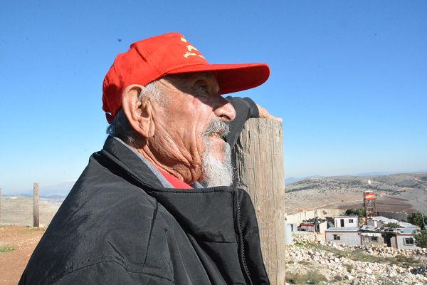 バジ氏はイスラエル国境をうらめしげに眺めた。写真右奥に見えるのはレバノン軍基地。=6日、ヴェント・ジュバイル村 写真:筆者=