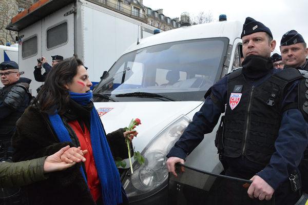 機動隊員にバラの花をプレゼントしようとする参加者。抗議の意志表示だ。自主規制が当たり前の日本では見かけない光景である。 =12日、凱旋門そば 写真:筆者=
