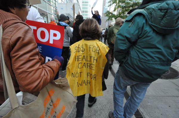 「財源を健康保険に使え、戦争に使うな」と訴えてデモ行進する米国市民。=2011年、ウォール街 撮影:筆者=