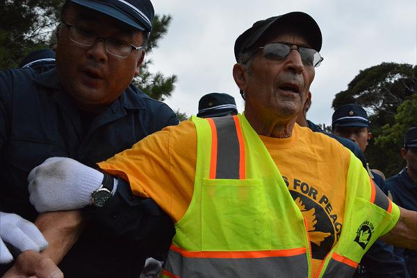 機動隊員に腕をつかまれ強制排除される米退役軍人。=1日午前9時30分頃、東村高江 撮影:筆者=