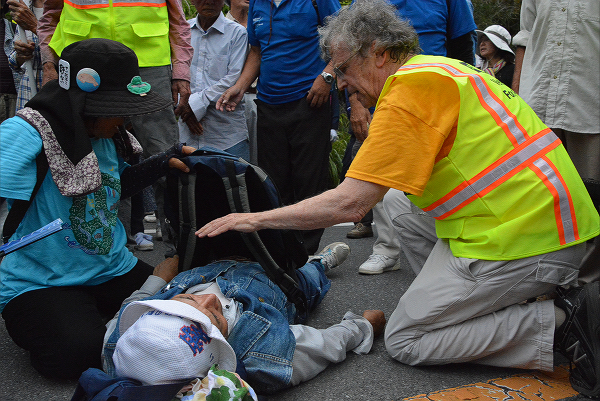 倒れた住民の容体を診る元看護兵。=1日午前9時45分頃、東村高江 撮影:筆者=