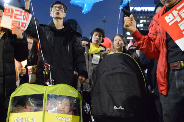 ベビーカーを押すイクメンも最前線で「朴クネ退陣」を叫んだ。=11月12日、ソウル 撮影:筆者=