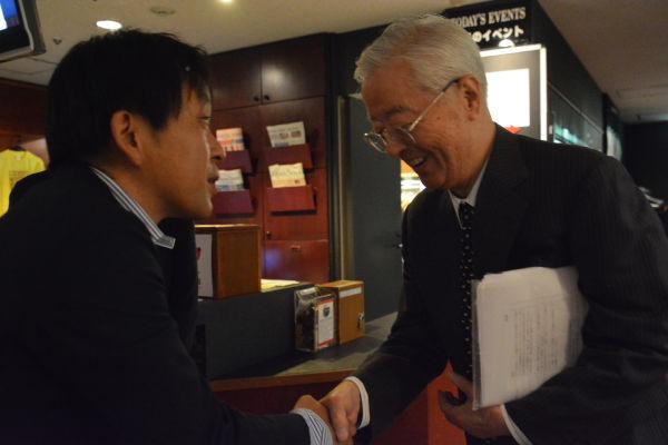 好敵手、相まみえる。日本会議会長の田久保忠衛・杏林大学名誉教授と握手する『日本会議の研究』著者の菅野完氏。=2016年7月、日本外国特派員協会 撮影:筆者=