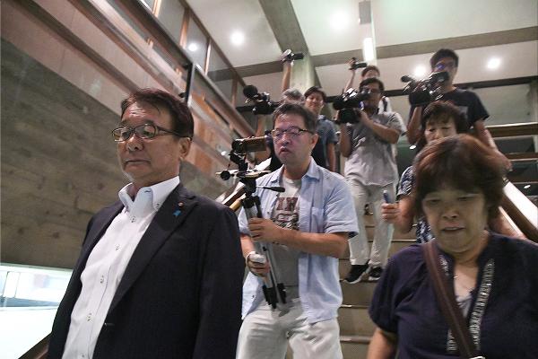 シャットアウトされた市民とメディアは山本議員(左)を出待ちして追った。=31日夕、今治市民ホール 撮影:筆者=