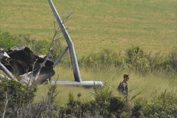 墜落、炎上したCH-53Eの残骸と事故処理の米兵=13日、東村高江 撮影:筆者=
